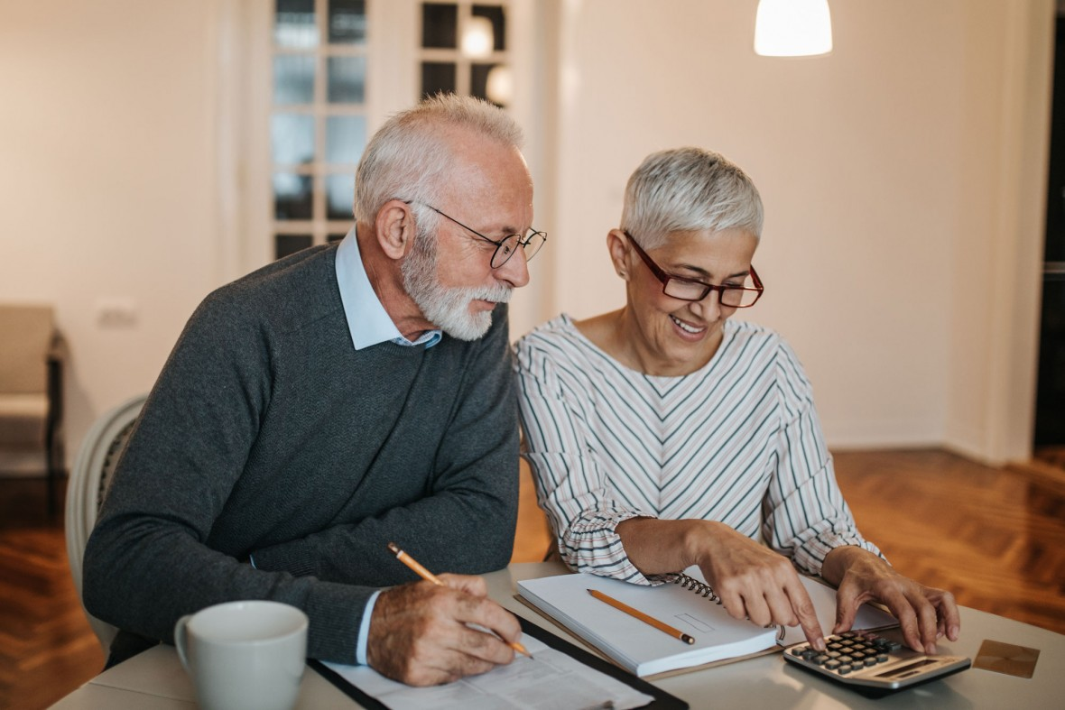 an older man and woman look at financial statements with a calculator